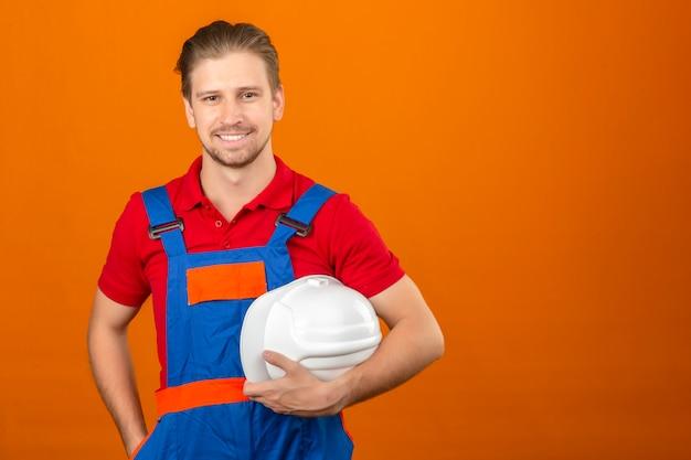 Jonge bouwersmens in de veiligheidshelm van de bouw eenvormige holding ter beschikking met grote glimlach op gezicht die zich over geïsoleerde oranje muur met exemplaarruimte bevinden