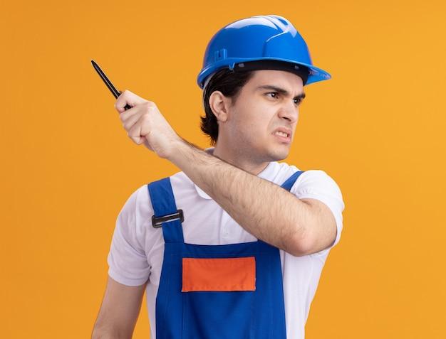 Jonge bouwersmens in eenvormige bouw en de pen van de veiligheidshelmholding die opzij met boos gezicht kijken dat zich over oranje muur bevindt