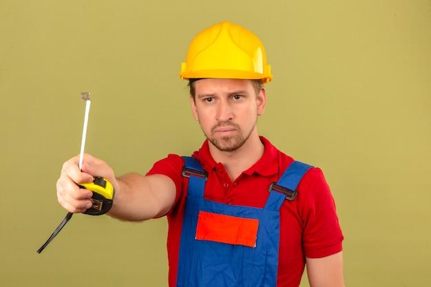 Jonge bouwersmens in eenvormige bouw en veiligheidshelm die aan iemand meetlint met ernstig gezicht over geïsoleerde groene muur geven