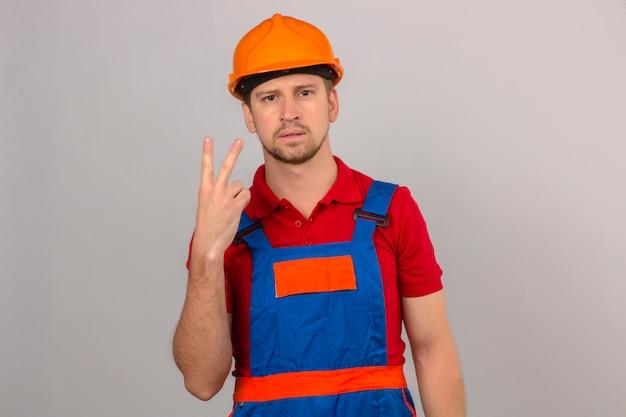 Jonge bouwersmens in eenvormige bouw en veiligheidshelm die en met vingers nummer twee met ernstig gezicht over geïsoleerde witte muur tonen benadrukken