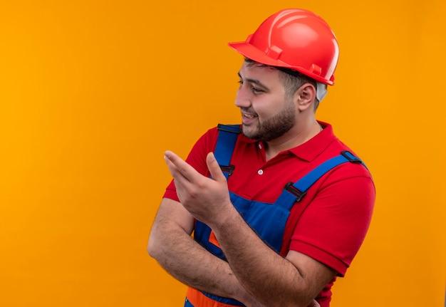 Jonge bouwersmens in eenvormige bouw en veiligheidshelm die opzij het opheffen van de hand kijken als het stellen van vraag