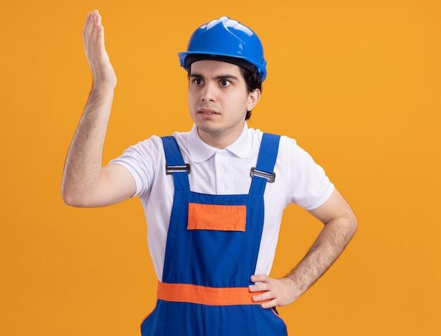 Jonge bouwersmens in eenvormige bouw en veiligheidshelm die opzij verward het opheffen dient ongenoegen in die zich over oranje muur bevindt