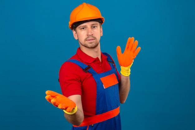 Jonge bouwersmens in eenvormige bouw en veiligheidshelm die verward gebaar met handen en uitdrukking maken als vraag over geïsoleerde blauwe muur