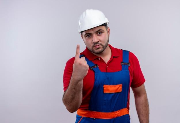 Jonge bouwersmens in eenvormige bouw en veiligheidshelm die wijsvinger met boos gezicht tonen