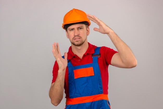 Jonge bouwersmens in eenvormige bouw en veiligheidshelm het gesturing met handen die de maatsymbool van het grootteteken over geïsoleerde witte muur tonen