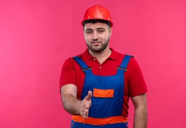 Jonge bouwersmens in eenvormige bouw en veiligheidshelmgroet met iemand die hand aanbiedt