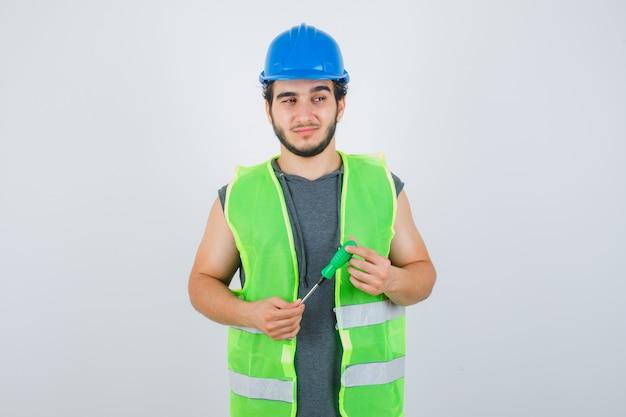Jonge bouwersmens in uniform die schroevendraaier houdt terwijl hij weg kijkt en nadenkend, vooraanzicht kijkt.
