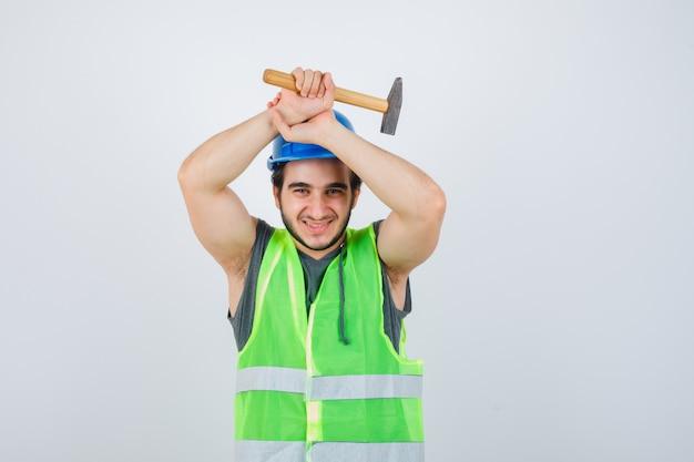 Jonge bouwersmens in uniforme werkkleding die hamer boven het hoofd houdt en vreugdevol, vooraanzicht kijkt.