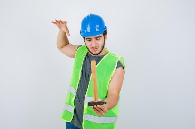 Jonge bouwersmens in uniforme werkkleding die hamer houdt terwijl hij hand opheft en voorzichtig, vooraanzicht kijkt.