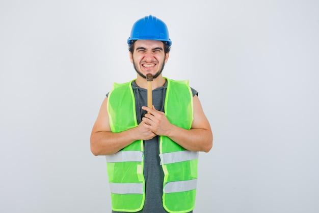 Jonge bouwersmens in uniforme werkkleding die hamer onder kin houdt en vrolijk, vooraanzicht kijkt.