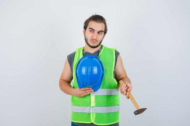 Jonge bouwersmens met hamer en helm in uniform werkkleding en peinzend, vooraanzicht op zoek.
