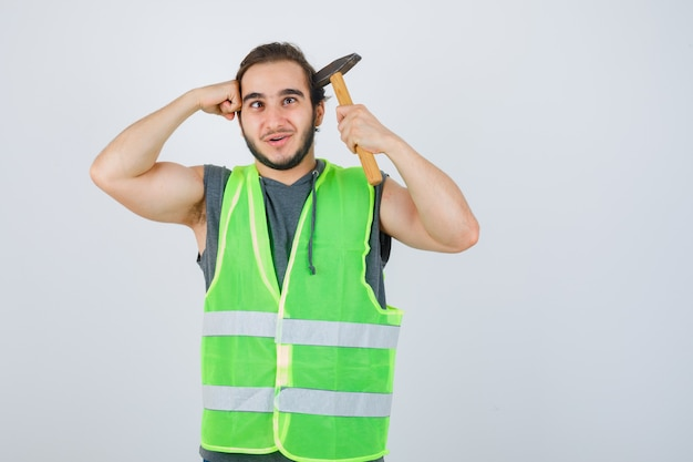 Jonge bouwersmens met hamer en vuist op hoofd in uniform werkkleding en op zoek vreugdevol, vooraanzicht.