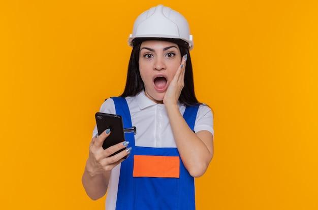 Jonge bouwersvrouw in bouwuniform en smartphone van de veiligheidshelmholding