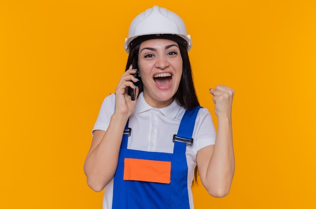 Jonge bouwersvrouw in bouwuniform en veiligheidshelm blij en opgewonden gebalde vuist tijdens het praten over de mobiele telefoon die zich over de oranje muur bevindt