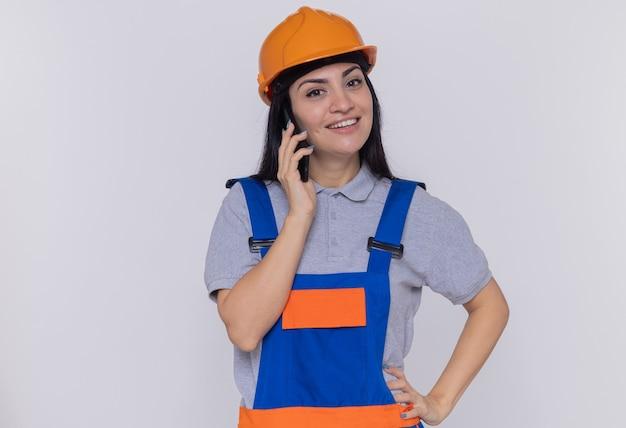 Jonge bouwersvrouw in bouwuniform en veiligheidshelm die aan voorzijde glimlachen terwijl het spreken op mobiele telefoon zich over witte muur bevindt
