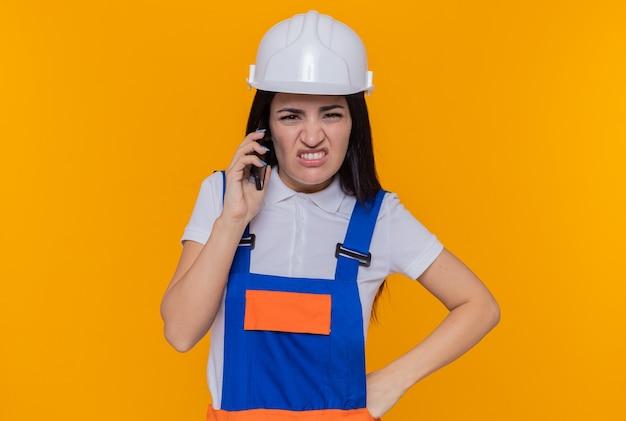 Jonge bouwersvrouw in bouwuniform en veiligheidshelm die geïrriteerd en ontevreden kijken tijdens het praten op mobiele telefoon die zich over oranje muur bevindt