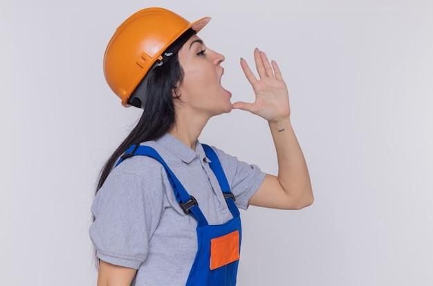 Jonge bouwersvrouw in bouwuniform en veiligheidshelm die iemand schreeuwen die overhandigt mond die zich over witte muur bevindt