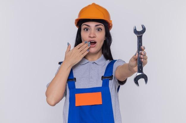 Jonge bouwersvrouw in bouwuniform en veiligheidshelm die moersleutel houden die voorzijde verbaasd en verrast bekijken die mond bedekken met hand die zich over witte muur bevindt