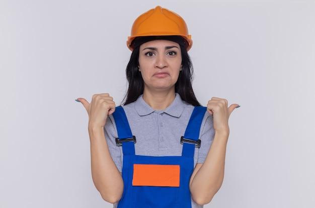Jonge bouwersvrouw in bouwuniform en veiligheidshelm die naar voorkant kijkt die met duimen naar achteren wijst en wrange mond met teleurgestelde uitdrukking maakt die zich over witte muur bevindt
