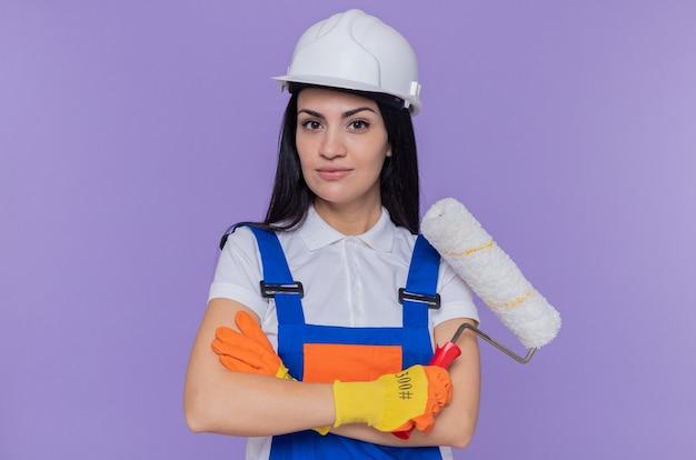 Jonge bouwersvrouw in bouwuniform en veiligheidshelm die rubberhandschoenen dragen die verfroller houden die voorzijde met ernstige zekere uitdrukking bekijken die zich over purpere muur bevinden