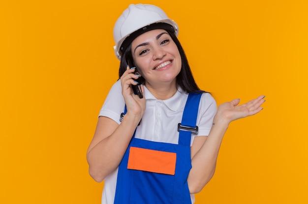 Jonge bouwersvrouw in bouwuniform en veiligheidshelm die voorzijde glimlachend opheffend wapen bekijken terwijl het spreken op mobiele telefoon die zich over oranje muur bevindt
