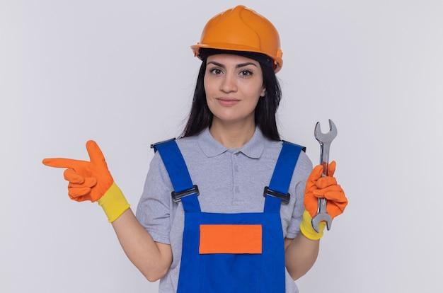 Jonge bouwersvrouw in bouwuniform en veiligheidshelm in rubberen handschoenen met moersleutel wijzend met wijsvinger naar de zijkant glimlachend zelfverzekerd staande over witte muur