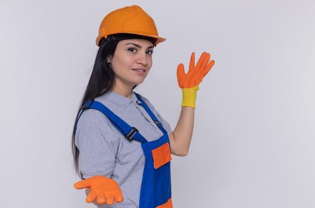 Jonge bouwersvrouw in bouwuniform en veiligheidshelm in rubberhandschoenen die voorzijde glimlachend zelfverzekerd voorstellen met wapens bekijken die zich over witte muur bevinden
