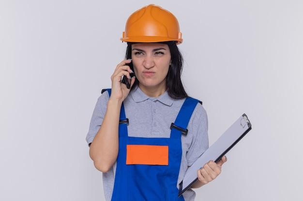 Jonge bouwersvrouw in bouwuniform en veiligheidshelm met klembord die ontevreden kijkt terwijl het spreken op mobiele telefoon die zich over witte muur bevindt