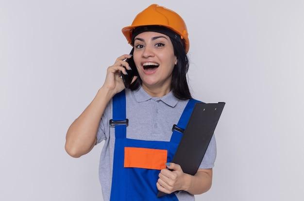 Jonge bouwersvrouw in bouwuniform en veiligheidshelm met klembord die vrolijk glimlachen terwijl het spreken op mobiele telefoon die zich over witte muur bevindt