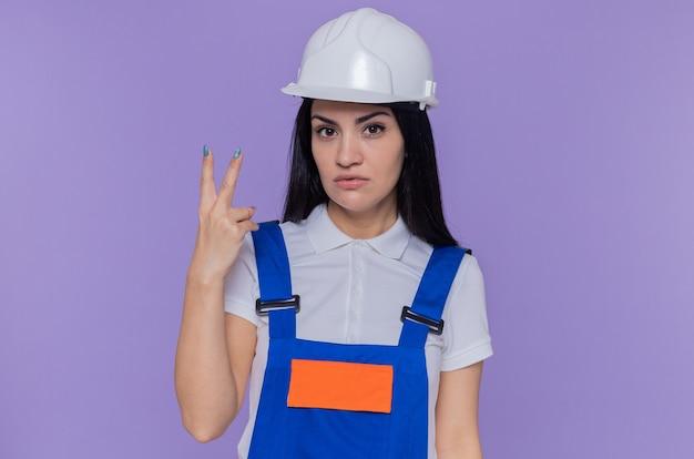 Jonge bouwersvrouw in bouwuniform en veiligheidshelm