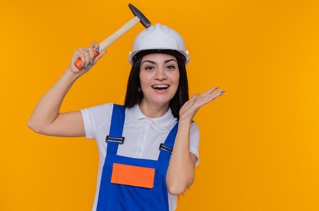 Jonge bouwersvrouw in eenvormige bouw en de hamer van de veiligheidshelmholding camera bekijken