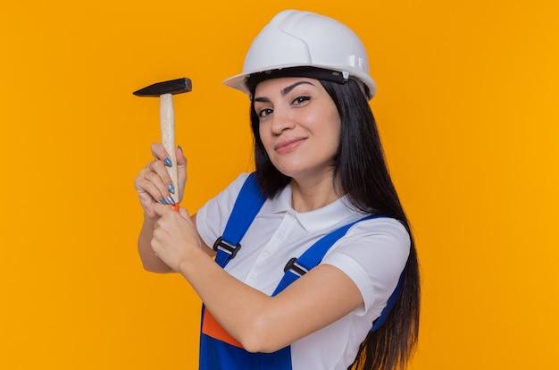 Jonge bouwersvrouw in eenvormige bouw en de hamer van de veiligheidshelmholding die voorzijde met glimlach op gezicht bekijken die zich over oranje muur bevinden