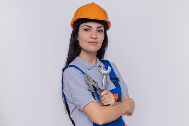 Jonge bouwersvrouw in eenvormige bouw en de holdingsmoersleutel en de buigtang van de veiligheidshelm die voorzijde glimlachend zelfverzekerd over witte muur bekijken