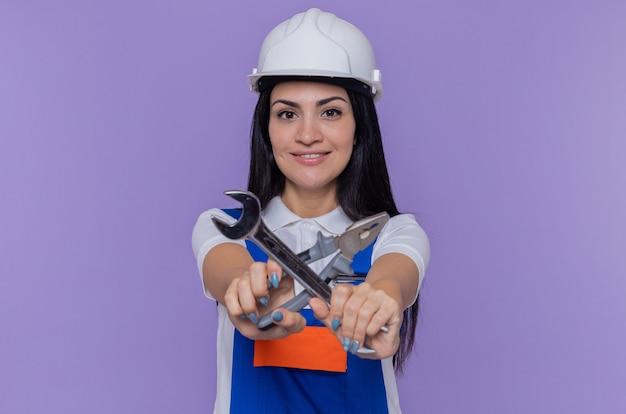 Jonge bouwersvrouw in eenvormige bouw en de moersleutel en de tang van de veiligheidshelm die voorzijde kruisen die handen bekijken die zelfverzekerd over purpere muur glimlachen