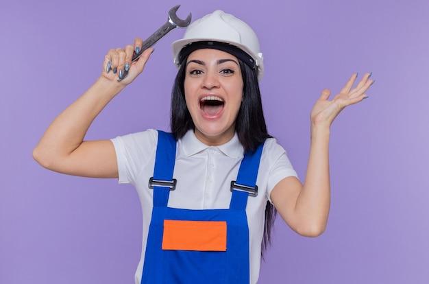 Jonge bouwersvrouw in eenvormige bouw en de moersleutel van de veiligheidshelmholding die wapen opheffen dat blij en opgewonden schreeuwen over purpere muur