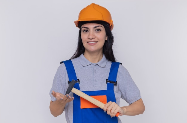 Jonge bouwersvrouw in eenvormige bouw en veiligheidshelm die een hamer slingeren die voorzijde glimlachend zelfverzekerd over witte muur kijken