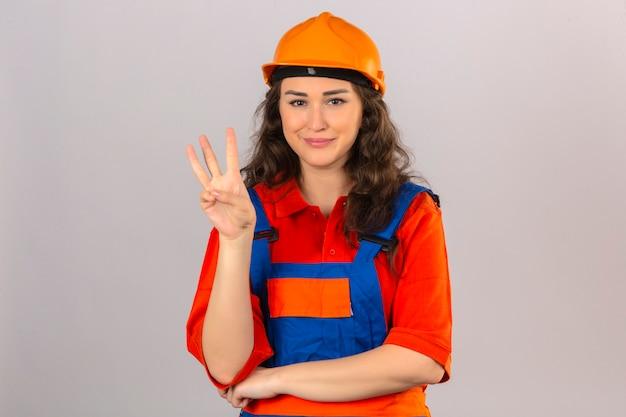 Jonge bouwersvrouw in eenvormige bouw en veiligheidshelm die het vrolijke tonen glimlachen en met vingers nummer drie benadrukken die zeker en gelukkig over geïsoleerde witte muur kijken
