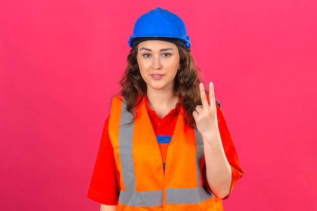 Jonge bouwersvrouw in eenvormige bouw en veiligheidshelm die het vrolijke tonen glimlachen en met vingers nummer twee benadrukken die zeker over geïsoleerde roze muur kijken