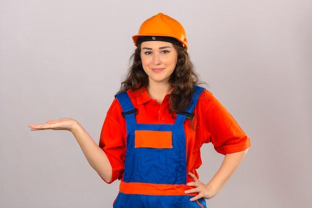 Jonge bouwersvrouw in eenvormige bouw en veiligheidshelm die het vrolijke voorstellen glimlachen en met palm van hand richten die de camera over geïsoleerde witte muur bekijken