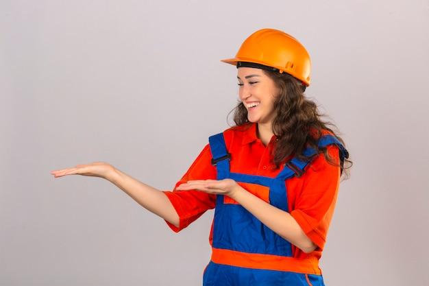 Jonge bouwersvrouw in eenvormige bouw en veiligheidshelm die het vrolijke voorstellen glimlachen en met palmen van handen richten die gelukkig over geïsoleerde witte muur kijken