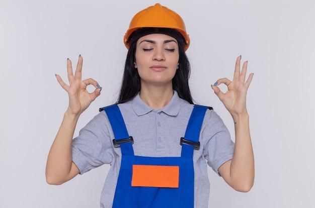 Jonge bouwersvrouw in eenvormige bouw en veiligheidshelm die meditatiegebaar maken