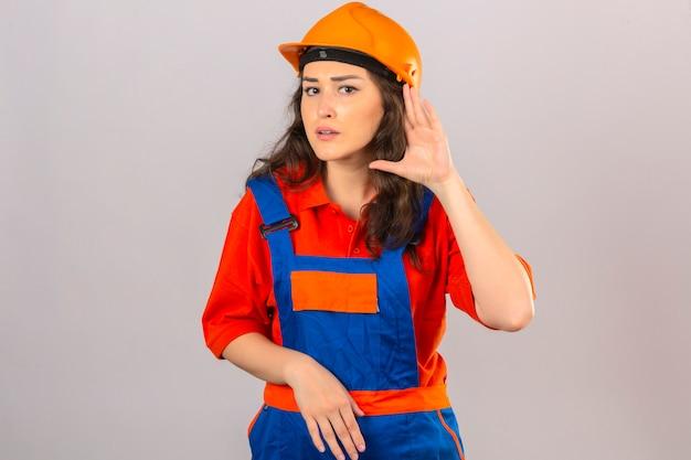 Jonge bouwersvrouw in eenvormige bouw en veiligheidshelm die met hand over oor glimlachen het luisteren een hoorzitting aan gerucht of roddel over geïsoleerde witte muur