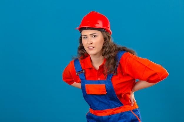 Jonge bouwersvrouw in eenvormige bouw en veiligheidshelm die ongelukkig en aan rugpijn over geïsoleerde blauwe muur kijken kijken