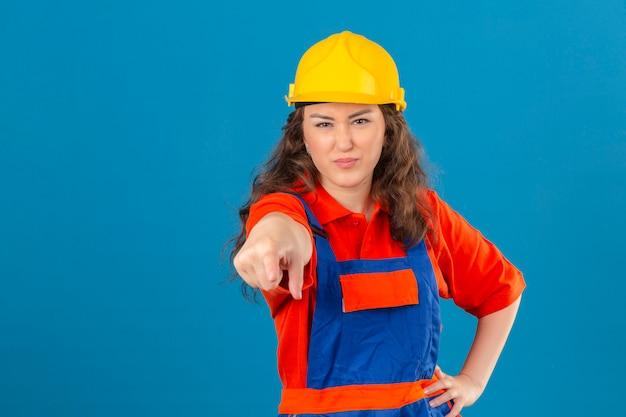 Jonge bouwersvrouw in eenvormige bouw en veiligheidshelm die ontevreden en gefrustreerd aan de camera boos en woedend met u over geïsoleerde blauwe muur richten