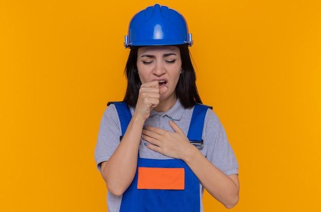 Jonge bouwersvrouw in eenvormige bouw en veiligheidshelm die onwel hoesten in vuist die zich over oranje muur bevindt
