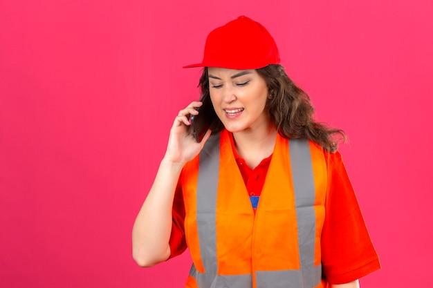 Jonge bouwersvrouw in eenvormige bouw en veiligheidshelm die op mobiele telefoon spreken in beklemtoond met agressieve gelaatsuitdrukking over geïsoleerde roze muur