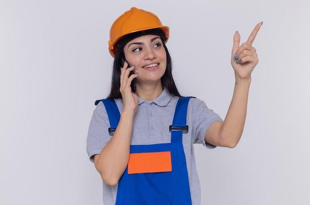 Jonge bouwersvrouw in eenvormige bouw en veiligheidshelm die opzij kijken