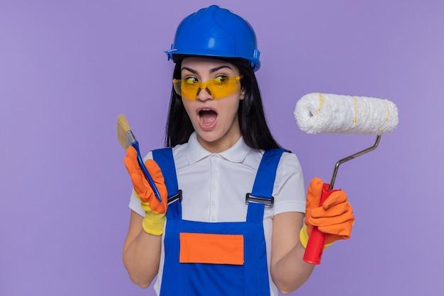 Jonge bouwersvrouw in eenvormige bouw en veiligheidshelm die rubberhandschoenen dragen