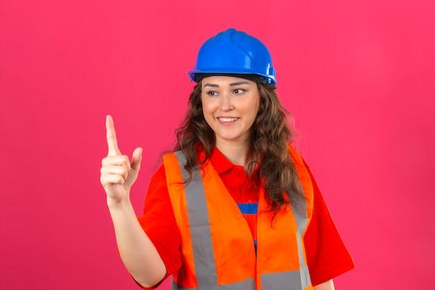 Jonge bouwersvrouw in eenvormige bouw en veiligheidshelm die tonend nummer één met vingers over geïsoleerde roze muur glimlachen