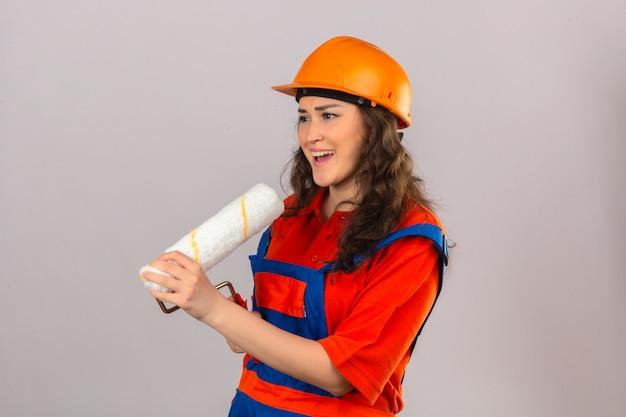 Jonge bouwersvrouw in eenvormige bouw en veiligheidshelm die verfrol gebruiken als pret van het microfoon zingende lied bij het werkconcept over geïsoleerde witte muur